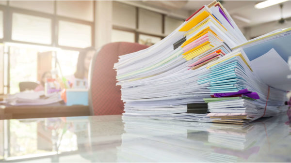 Stack of papers piled up on an office desk