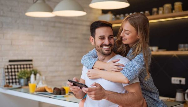 husband and wife in kitchen hugging