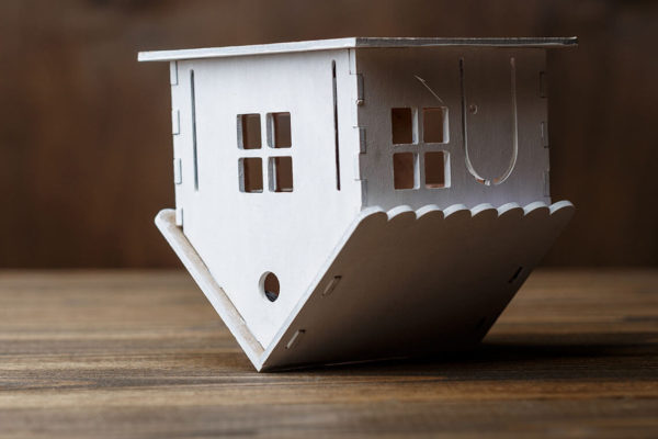 simple wooden model of a house balancing upside down on its roof