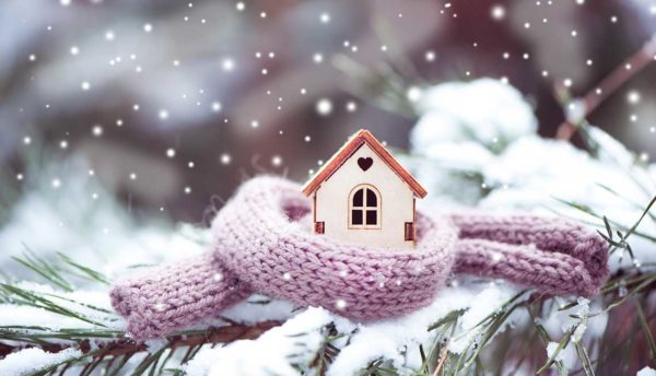 house in the snow with a scarf wrapped around it